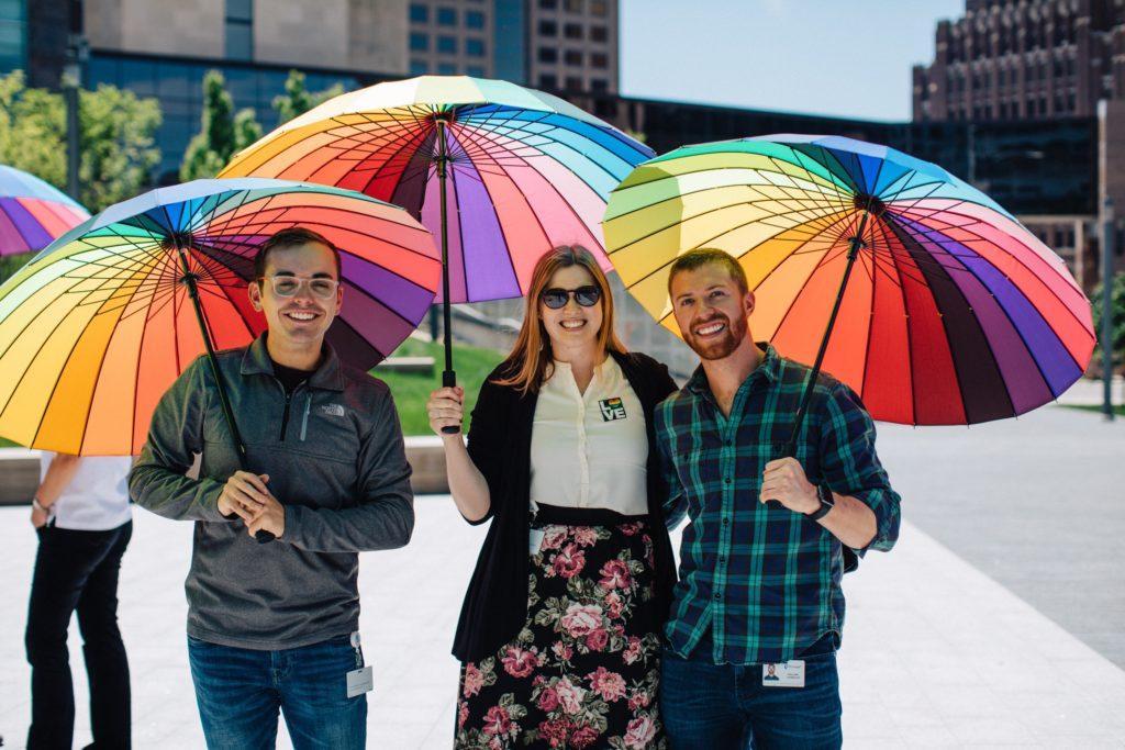 Three people holding large rainbow umbrellas outdoors.